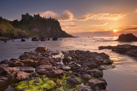 non: The ruins of the Dunluce Castle on the Causeway Coast of Northern Ireland. Photographed at sunset.
