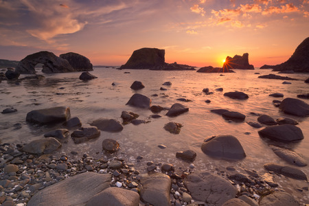 natural arch: Sea stacks and natural arch along the coast near Ballintoy Harbour on the Causeway Coast of Northern Ireland at sunset.