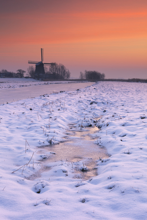 noord: Typical Dutch polder landscape with a traditional windmill. Photographed in winter at sunrise.
