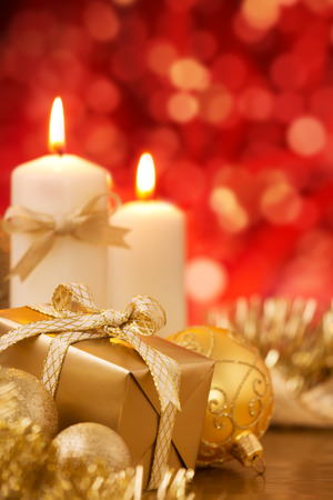 Red and golden Christmas baubles, a gift and candles in front of defocused red lights. Stock Photo