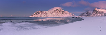 Alpenglow at the rocky beach of Skagsanden on the Lofoten in northern Norway, photographed at dusk in winter.
