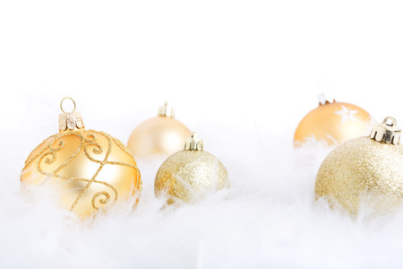 feathery: Golden Christmas baubles on a soft feathery surface with a white background. Stock Photo