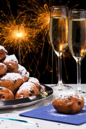 Oliebollen, traditional Dutch pastry for New Years Eve and two glasses of champagne. Stock Photo