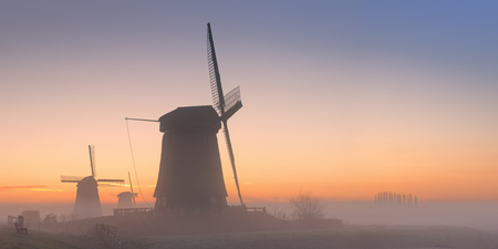 schermerhorn: Traditional Dutch windmills on a beautiful frosty and foggy morning.