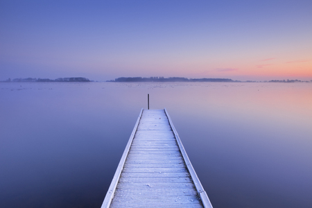 jetty: A quiet lake in The Netherlands with a jetty on an early winter morning.