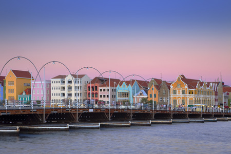 The colored houses and the Queen Emma pontoon bridge of Willemstad, Curacao in the Netherlands Antilles at dusk.