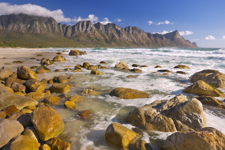 A rocky beach at the Kogel Bay in South Africa with the Kogelberg Mountains in the back. Photographed on a very windy but sunny day.