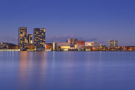 The skyline of the city of Almere in The Netherlands, photographed from across the water at dusk.