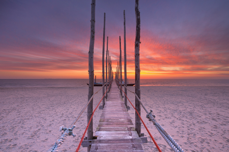 Spectacular sunrise colours over a jetty on a beach on the island of Texel in The Netherlands. Stock Photo