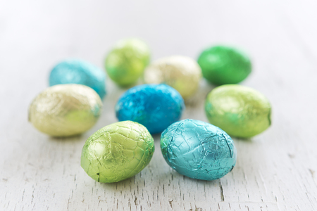 lit collection: Close up of an assortment of chocolate Easter eggs on a rustic wooden background.
