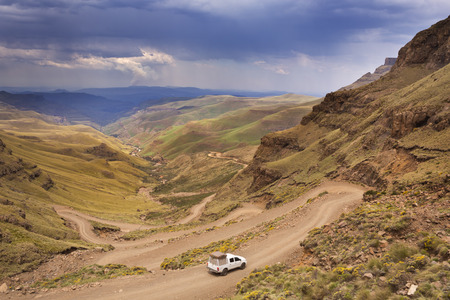 A car driving the hairpin turns of the Sani Pass on the border of South Africa and Lesotho. Stock Photo