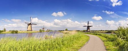 A path along traditional Dutch windmills on a bright and sunny day at the Kinderdijk in The Netherlands.