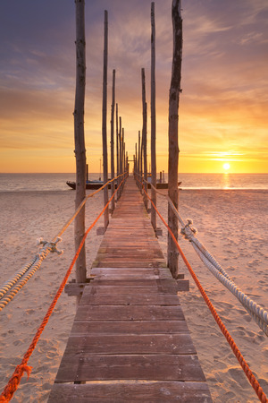 noord: Spectacular sunrise colours over a jetty on a beach on the island of Texel in The Netherlands. Stock Photo