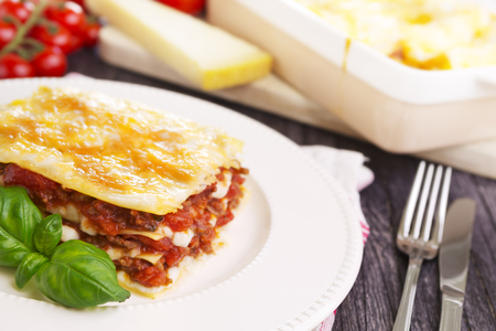 A portion of homemade lasagna on a plate on a brightly lit table. Stock Photo