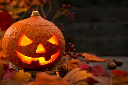 Burning Jack O'Lantern op een rustieke tafel met herfst decoraties, donker verlicht. Stockfoto