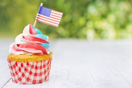 Red-white-and-blue cupcakes with American flags on an outdoor table.