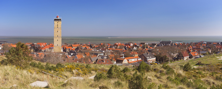 West-Terschelling village with the Brandaris lighthouse on the island of Terschelling in The Netherlands on a bright and sunny day.