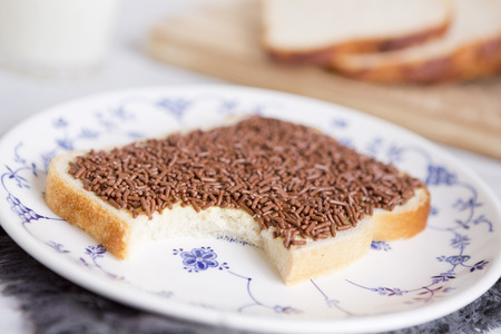 A sandwich with chocolate sprinkles or a 'boterham met hagelslag', Dutch traditional food. Фото со стока