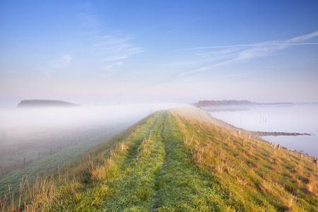 A typical Dutch polder landscape with a dike along a lake. Photographed at the Veerse Meer in the province of Zeeland on a foggy morning. Stock Photo