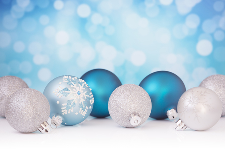 Blue and silver Christmas baubles in front of defocused purple and white lights.