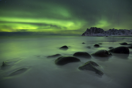 The aurora borealis over Uttakleiv beach on the Lofoten in northern Norway in winter. Stock Photo