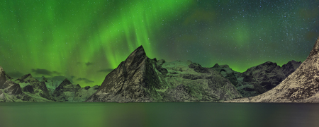 Panorama of the aurora borealis over a fjord on the Lofoten in northern Norway in winter.