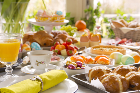 Breakfast or brunch table filled with all sorts of delicious delicatessen ready for an Easter meal. 免版税图像 - 93561821