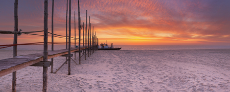 Spectacular sunrise colours over a jetty on a beach on the island of Texel in The Netherlands. Stockfoto