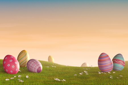 Decorated Easter eggs lying in the grass in a hilly landscape at sunset. Reklamní fotografie