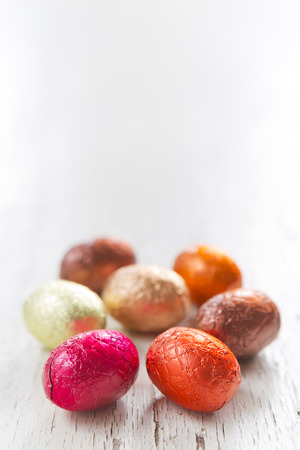 Close up of an assortment of chocolate Easter eggs on a rustic wooden background.