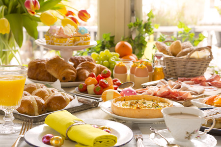 Breakfast or brunch table filled with all sorts of delicious delicatessen ready for an Easter meal.