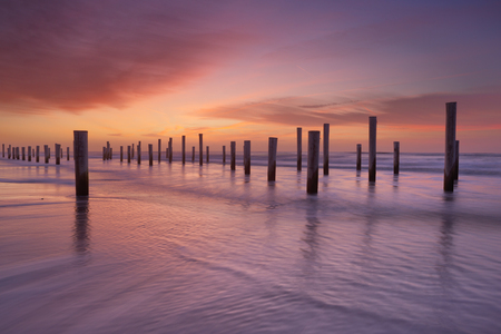 Wooden poles standing in the surf on the beach. Photographed at sunset. Stockfoto