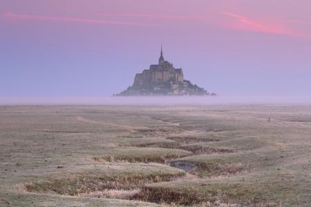 Le Mont Saint Michel in Normandy, France on a foggy morning at sunrise. Reklamní fotografie