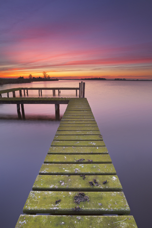 An old jetty on a lake in The Netherlands, photographed at sunset.