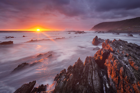 Spectacular sunset over the rocky coastline of the Tsitsikamma section of the Garden Route National Park, South Africa. Reklamní fotografie