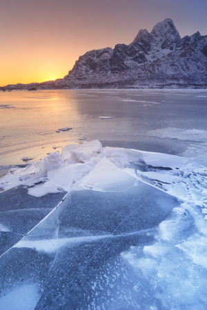 A frozen fjord on the Lofoten in northern Norway with the low midday sun behind the mountains.