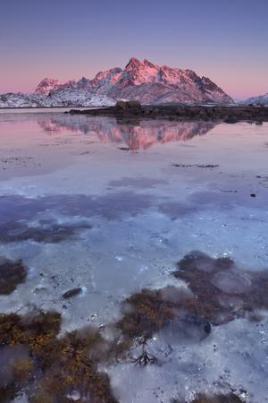 Los picos de las montañas se reflejan en el agua de las Lofoten, en el norte de Noruega, al atardecer.