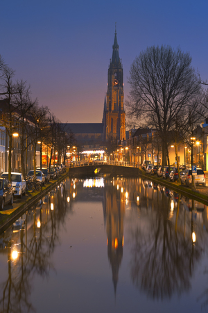 The New Church reflected in a canal in Delft in The Netherlands at night. Reklamní fotografie