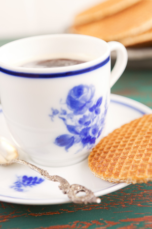 Cup of coffee with a Dutch stroopwafel cookie or caramel waffle.
