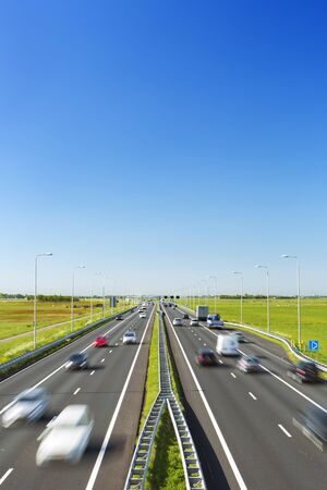 A highway with traffic through grassy fields on a bright and sunny day in The Netherlands.