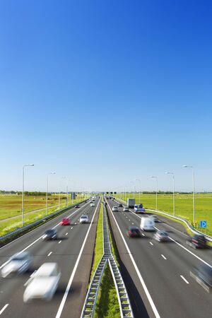 Eine Autobahn mit Verkehr durch Grasfelder an einem hellen und sonnigen Tag in den Niederlanden.
