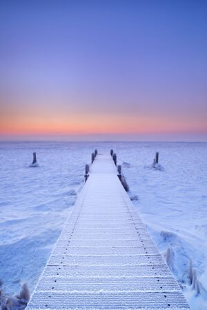 Jetty on a frozen lake. Photographed at sunrise on a record-breaking cold morning in The Netherlands.
