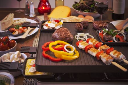 Swiss raclette or the Dutch variant 'gourmetten'. A table filled with ingredients for a dish that is usually served on celebratory evenings like Christmas or New Years Eve in The Netherlands. Foto de archivo