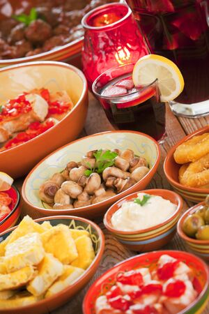A table filled with all sorts of Spanish tapas and sangria.