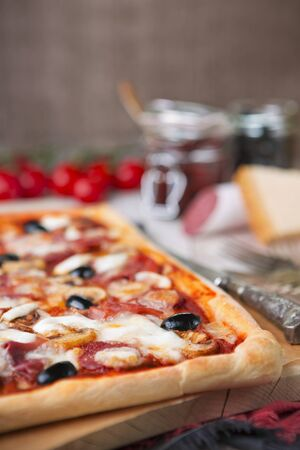 Homemade rectangular pepperoni pizza on a rustic table with ingredients.