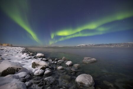 The aurora borealis over a moonlit fjord in northern Norway in winter.