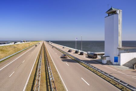 Traffic on the Afsluitdijk on a sunny day in The Netherlands. The Afsluitdijk is a dike over 32km damming off the former Zuiderzee, a salt water inlet of the North Sea. The monumental tower by architect Dudok marks the spot where the dike was closed in 1932.