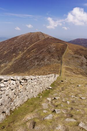 The Mourne Wall and the peak of Slieve Meelmore in the Mourne Mountains in Northern Ireland. Stock Photo
