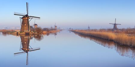 Traditional Dutch windmills reflected in perfectly still water on a cold morning in winter, at the Kinderdijk in The Netherlands. Stock Photo