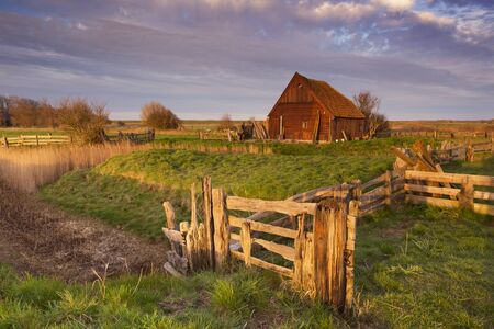 An old traditional sheep barn or 'schapenboet' on the island of Texel in The Netherlands in early morning sunlight. Imagens